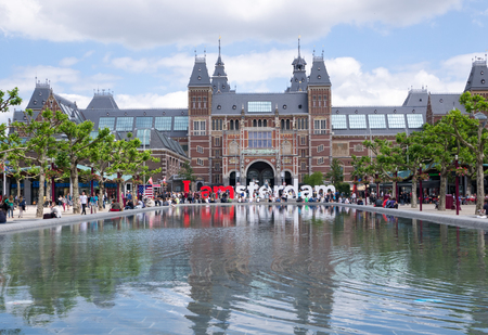 sit around: AMSTERDAM - 2 JULY 2014:Tourists sit around the I Love Amsterdam sign at national Rijksmuseum, a popular tourist destination. It attracts more than 2 million visitors each year from all over the world