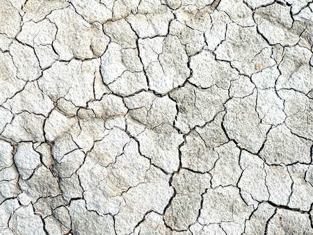 barren: Cracked and barren grey colored clay earth