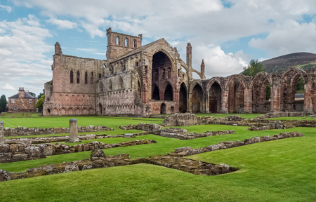 The ruins of pink colored Melrose Abbey in the Scottisch Borders region in Scotland