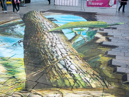 power giant: ALMERE, NETHERLANDS - 23 OCT. 2017: Street art by an unknown artists of a giant tree and leaf shows the power of 3D illusion. Once a year the city lets artists make paintings on the streets Editorial