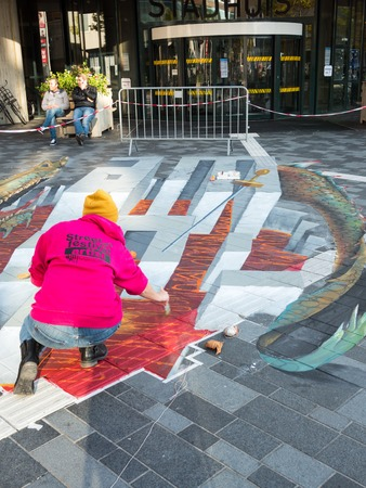 street painting: ALMERE, NETHERLANDS - 23 OCT. 2017: Unknown artist works on a street painting that shows the power of 3D optical illusion. Once a year the city of Almere allows artists to create street art