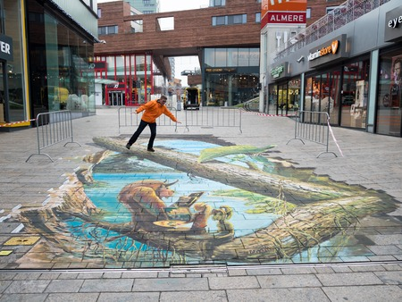 ALMERE, NETHERLANDS - 24 OCT. 2017: Unknown man shows the power of 3D optical illusion of a street painting of a scene from the tale Beauty and the Beast by an unknown artist, in Almere