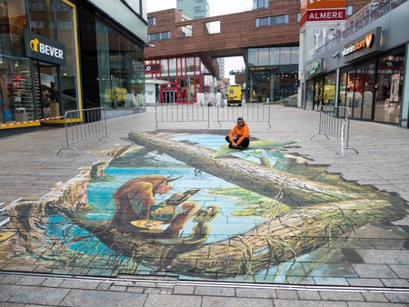 street painting: ALMERE, NETHERLANDS - 24 OCT. 2017: Unknown man shows the power of 3D optical illusion of a street painting of a scene from the tale Beauty and the Beast by an unknown artist, in Almere