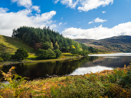 Loch Killin en las Tierras Altas de Escocia con el reflejo de los árboles y las montañas Monadhliath en el fondo Foto de archivo