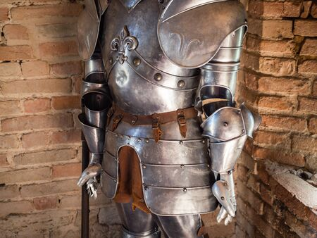 Detail of knight in medieval armor with battle axe against the backdrop of old stone walls