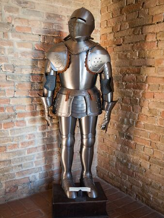 Knight in medieval armor with battle axe against the backdrop of old stone walls