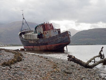 Abandoned fishing boat on a beach at Loch Linnhe near Corpach in the Ben Nevis region, Scotland Banque d'images
