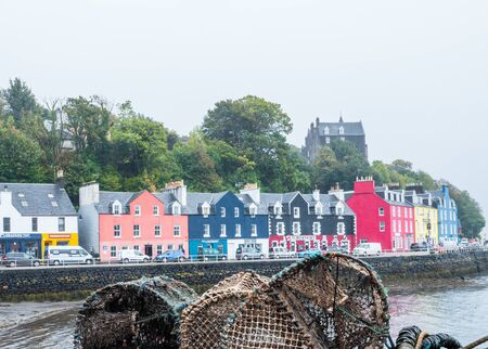 Fishing baskets on jetty and colorful houses along the main street of the town of Tobermory on the Isle of Mull, Scotland Banque d'images