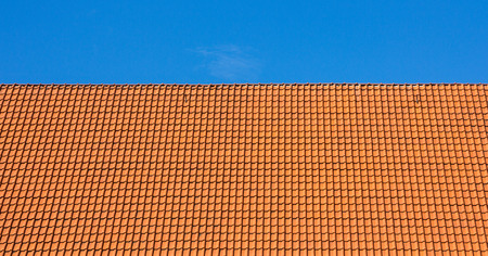 Red rooftop of tiles against blue sky photo