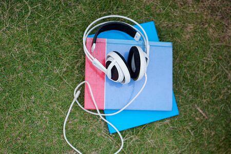 white headphone  on book the grass for listen the music Stock fotó