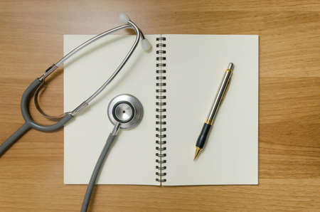 pen and stethoscope on open book