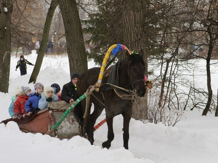 Children ride on horse in park on shrovetide in winter