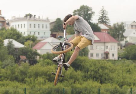 springboard: Lad hace salto con trampolín en la bicicleta con la ejecución del truco en el festival Ekshen deporte en la ciudad zona de Elice Lipeckoy
