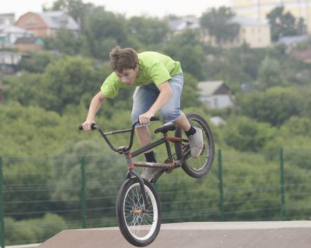 springboard: El muchacho hace salto con trampol�n en la bicicleta en el festival Ekshen deporte en la ciudad zona de Elice Lipeckoy