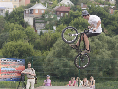 lad: Lad makes jump with springboard on bicycle with performance of the stunt on festival Ekshen sport in city Elice Lipeckoy area Editorial