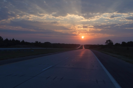 dawning: sun rays with clouds along highway
