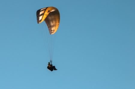 Riding the air on a yellow parachute photo
