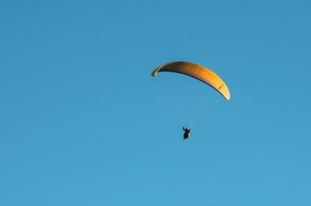 Yellow parachute gliding through the air photo