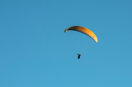 restraints: Yellow parachute gliding through the air