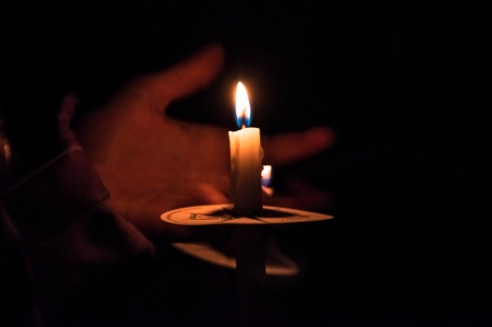 Hand holding burning candle