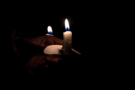 Hands holding burning candles photo