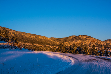 herman: Bend on a snow packed country road leading to the mountains Stock Photo
