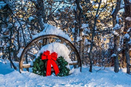herman: Christmas wreath on wagon wheel in snowy forest Stock Photo
