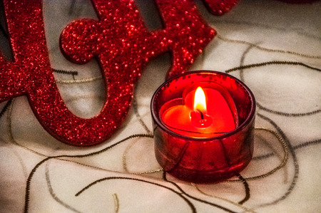 votive candle: Red votive candle on tablecloth Stock Photo