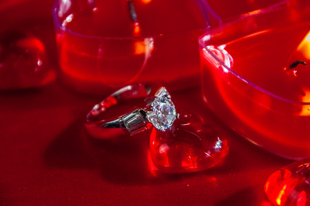 diamond candle: Heart shaped votive candles with diamond ring resting on red heart glass ornament Stock Photo