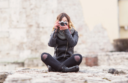 Hipster photographer girl in leather coat sitting with vintage DSLR camera