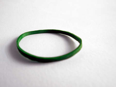 Green elastic band on a white background. Rubber bands are used for many things, art and craft and office work being among them