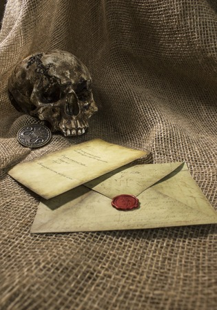 Damaged skull with a vintage letter, with a burlap background