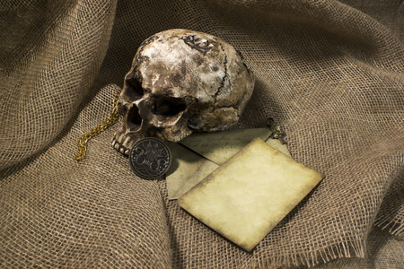 Damaged skull with a letter, with a burlap background