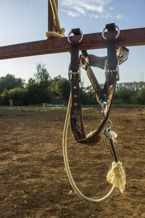 Horse harness hanging on the fence of a horse farm.