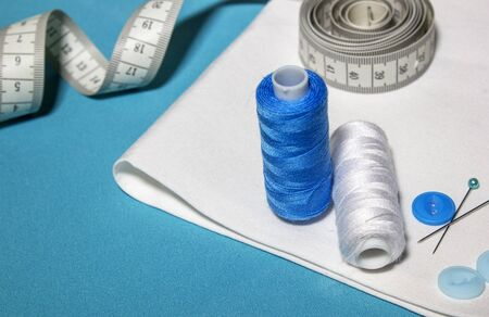 Blue textured background with sewing tools, copy space on background. Frame with sewing tools and accessories. Top view.