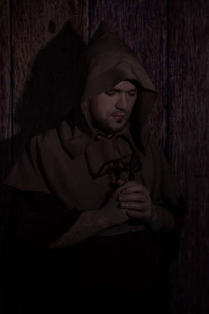 Medieval monk praying with closed eyes. mysterious Catholic monk