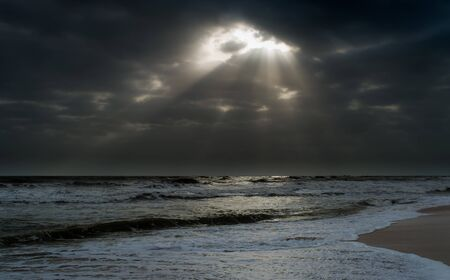 Sunshine pouring over the sea through the clouds view from beach of somnath temple Gujarat India
