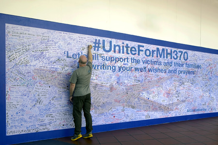 hijacked: Kuala Lumpur, Malaysia 15 Mar 2014 - MH370 missing plane, Malaysians showing support by writing prayers on a wall at a shopping complex