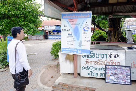 Chiang Rai, Thailand, 6 June 2014 - A tourist looking at advertisement for a boat trip at Thailand-Myanmar-Laos Golden Triangle