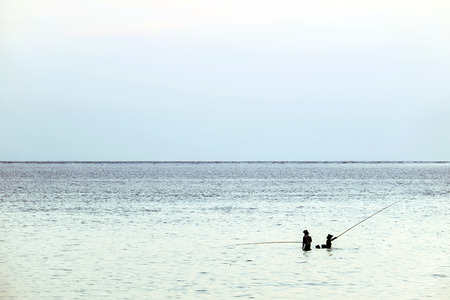Silhouette of 2 anglers by the shallow sea with blue skyline and water  版權商用圖片