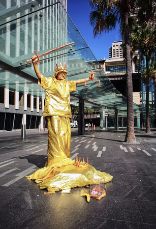 SYDNEY, AUSTRALIA - Sept 12, 2015 - Street performer mimicking statue-like post at tourist attraction area, Circular Quay