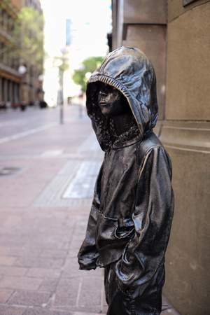 SYDNEY, AUSTRALIA - Sept 12, 2015 - A bronze sculpture of a boy with a hooded jacket at Barrack Street. Sculpture by Caroline Roth