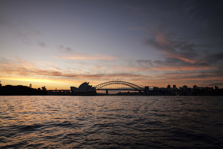 Silhouette of Sydney Opera House and Harbour Bridge during sunset