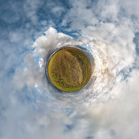 Little planet transformation of spherical panorama 360 degrees. Spherical abstract aerial view in field with awesome beautiful clouds. Curvature of space. Banco de Imagens