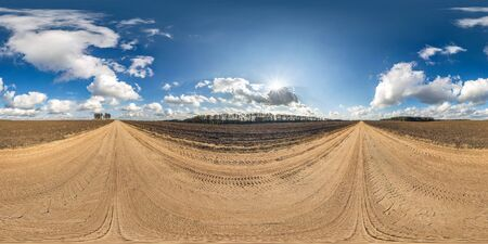 full seamless spherical panorama 360 degrees angle view on gravel road among fields in spring day with awesome clouds in equirectangular projection, ready for VR AR virtual reality content