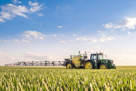 Landwirt, der im Frühjahr Weizenfeld mit Traktorspritze besprüht
