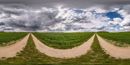 full seamless spherical hdri panorama 360 degree angle view on no traffic gravel road among fields with overcast sky before storm in equirectangular projection, ready for VR AR virtual reality content