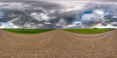 full seamless spherical hdri panorama 360 degrees angle view on wet gravel road among fields in spring day with storm clouds after rain in equirectangular projection, ready for VR AR content Stock fotó