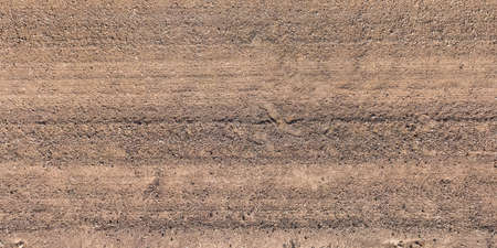 view from above on surface of gravel road with car tire tracks