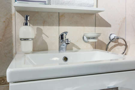 Ceramic Water tap sink with faucet with soap and shampoo dispensers in expensive loft bathroom or kitchen